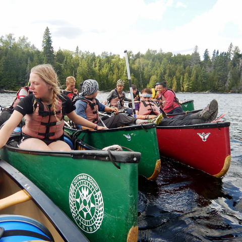 group-of-participants-holding-onto-canoes